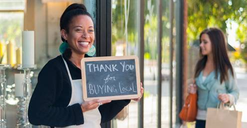 woman holding sign - thank you for buying locally